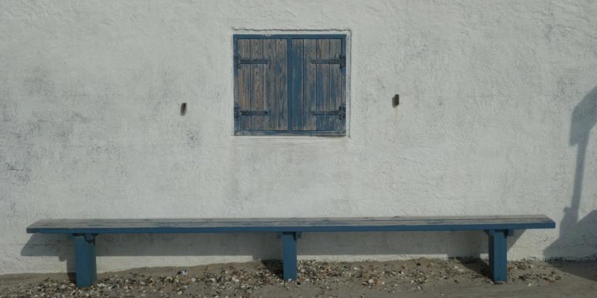 Unter einem Fenster lädt eine Bank zum Verweilen und Zuhören ein. Ellas Schreibwelt