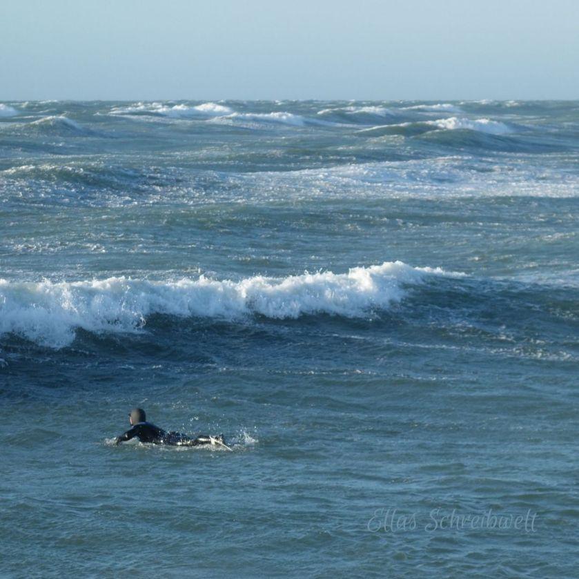 Ein Surfer wartet auf eine Welle